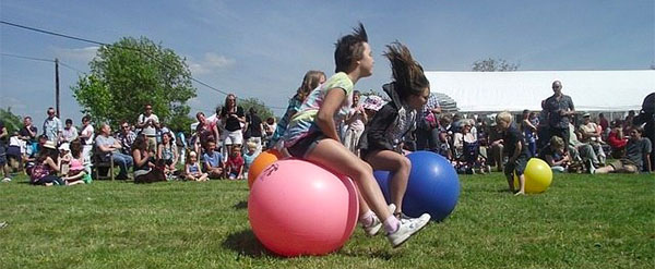 A photo of children racing on grass sitting on space hoppers
