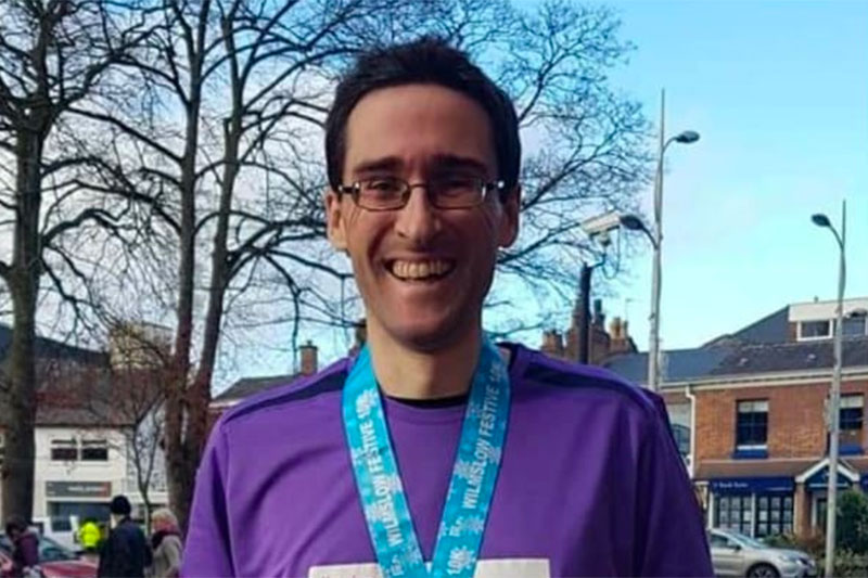 A photo of Manners Pimblett Personal Injury and Clinical Negligence Solicitor, Greg Hall in his running kit after crossing the line at he Wilmslow 10K