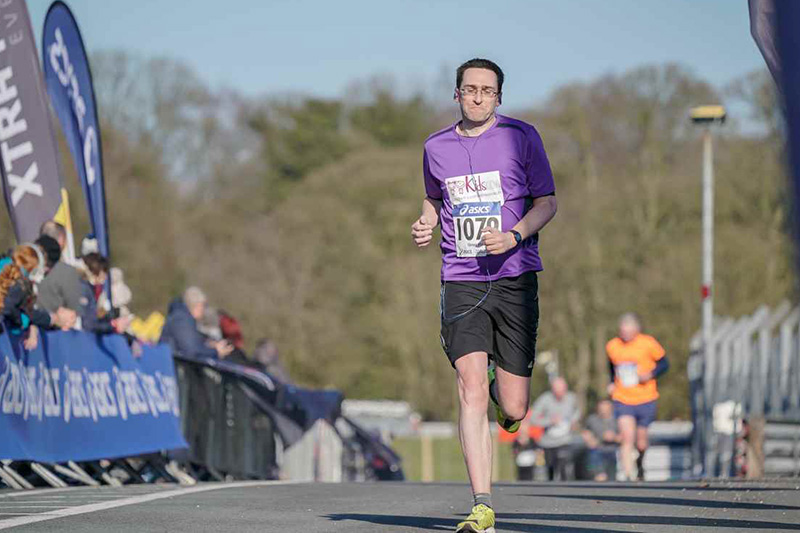 A photo of Manners Pimblett Personal Injury and Clinical Negligence Solicitor, Greg Hall, about to cross the finishing line at the Oulton Park 10K